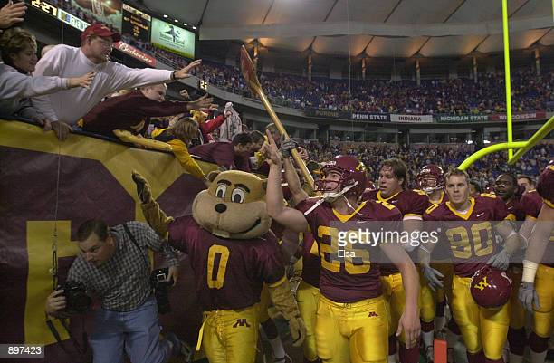 Place kicker Ryan Duffy of the Minnesota Golden Gophers leads the school mascot and a group of players carrying Paul Bunyan's Axe trophy of the...