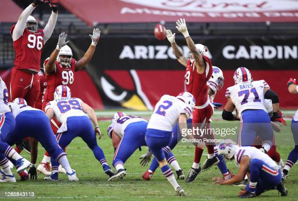 Place kicker Tyler Bass of the Buffalo Bills kicks a field goal as defensive end Angelo Blackson and defensive tackle Corey Peters of the Arizona...