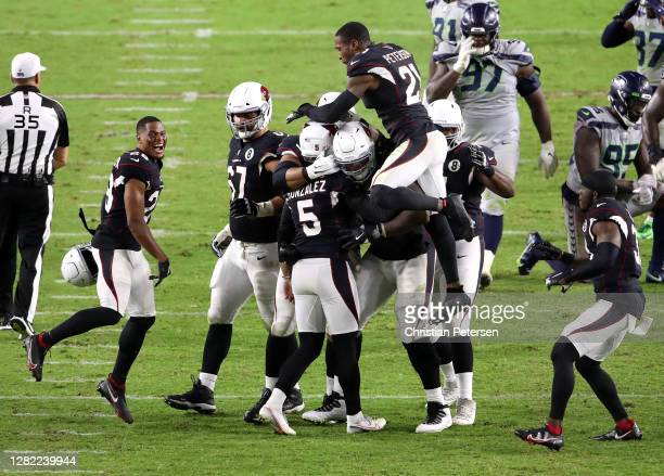 Place kicker Zane Gonzalez of the Arizona Cardinals is mobbed by teammates as defensive tackle Poona Ford and defensive end Benson Mayowa of the...