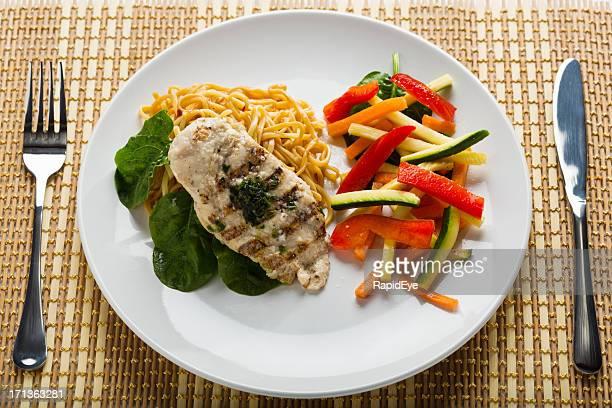 Table dressée avec basilic plat de poulet grillé et légumes sautés