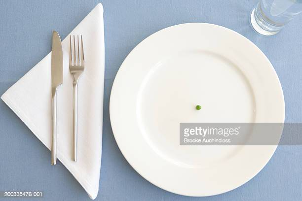 place setting with green pea in center of plate, overhead view - silverware stock pictures, royalty-free photos & images
