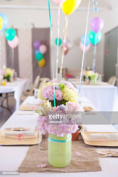 Place settings on party tables under balloons