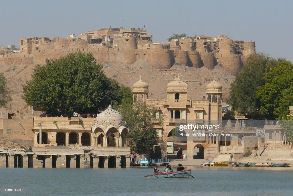 Placid boat ride with a view of Tilon-Ki-Pol gate and Jaisalmer fort from Gadi Sagar lake in Jaisalmer, Rajasthan, India : Foto de stock