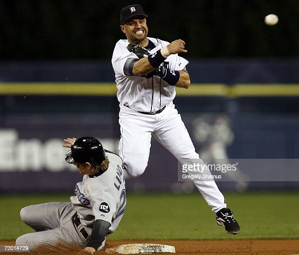 Placido Polanco of the Detroit Tigers turns a double play behind the slide of Adam Lind of the Toronto Blue Jays on September 26 2006 at Comerica...