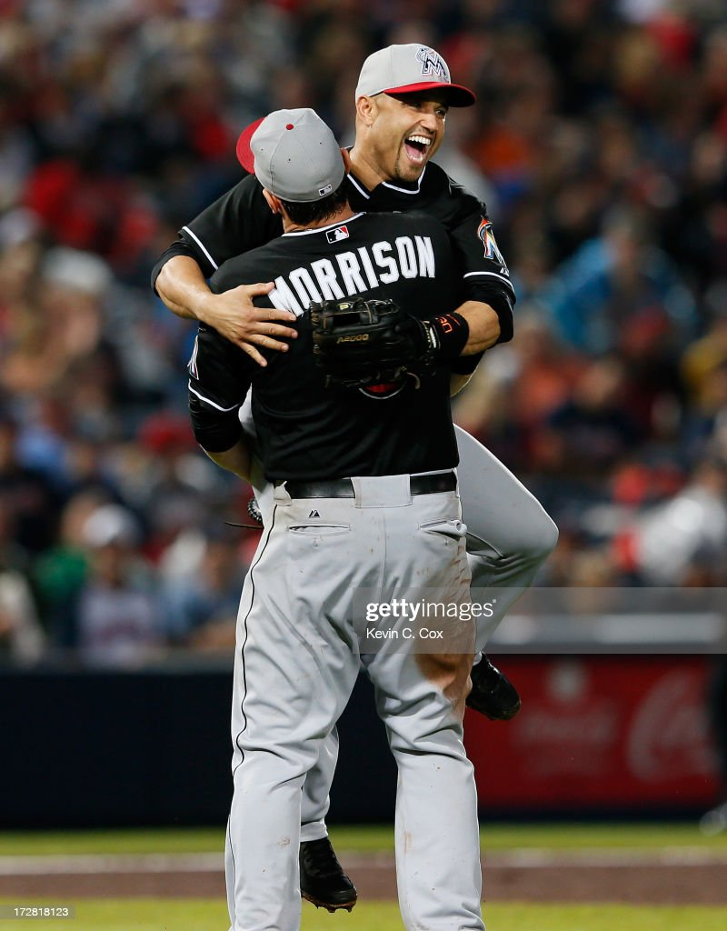 Placido Polanco #30 of the Miami Marlins celebrates with Logan Morrison #5 after their 4-3 win in the ninth inning over the Atlanta Braves at Turner Field on July 4, 2013 in Atlanta, Georgia.
