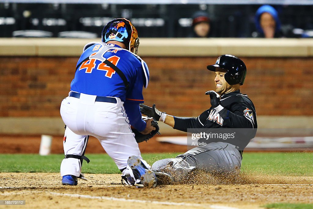 Placido Polanco #30 of the Miami Marlins is tagged out at home by John Buck #44 of the New York Mets in the eighth inning during their game on April 5, 2013 at Citi Field in the Flushing neighborhood of the Queens borough of New York City.