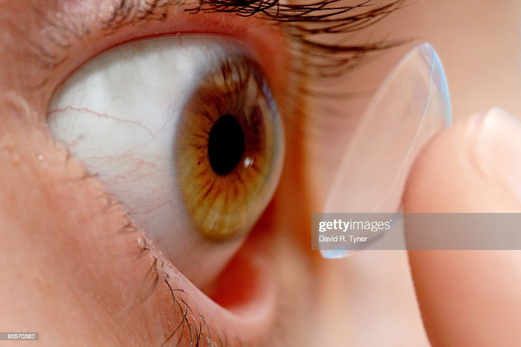 Placing a contact lens in an eye : ストックフォト