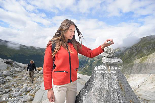 Placing a Stone on Mountain Cairn in Swiss Alps