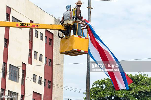 Placing decorative flags in Havana in preparation for Pope Francis visit. Yellow construction equipment on a sunny and hot day, workers wearing...