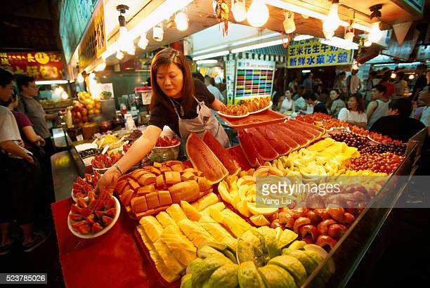 Placing Fruit on Display in Night Market