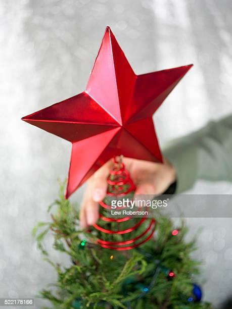 Placing Red Star atop Christmas Tree