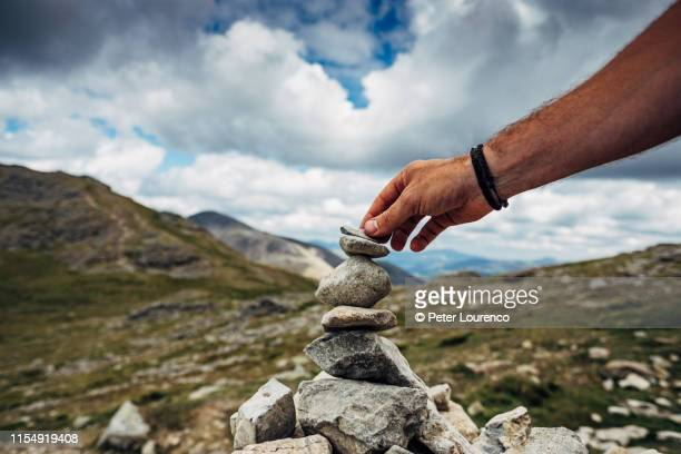 placing stone on cairn - peter lourenco stock pictures, royalty-free photos & images
