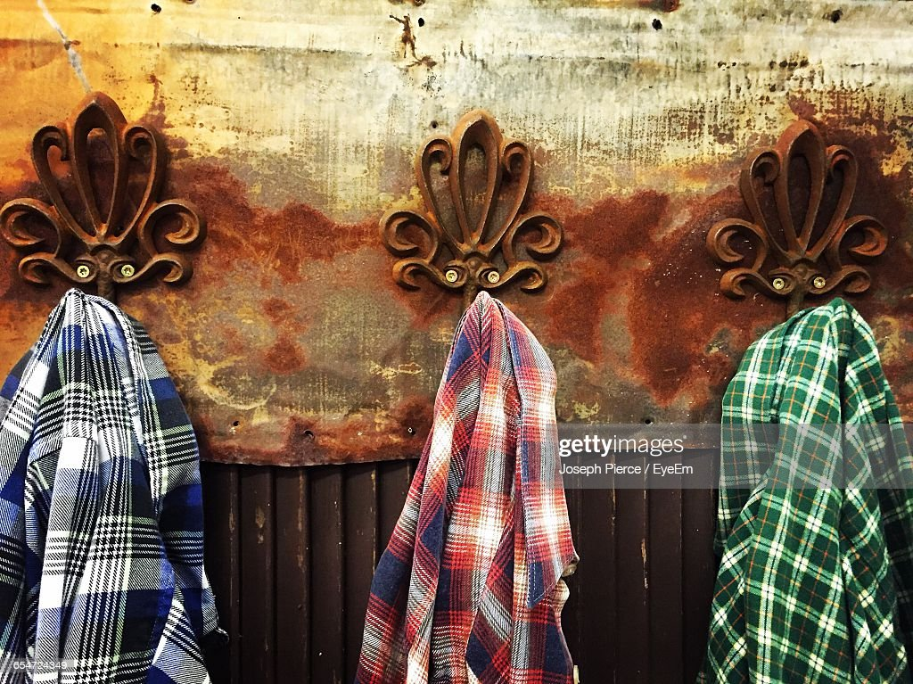 Plaid Shirts Hanging From Hooks Mounted On Rusty Wall : Stock-Foto
