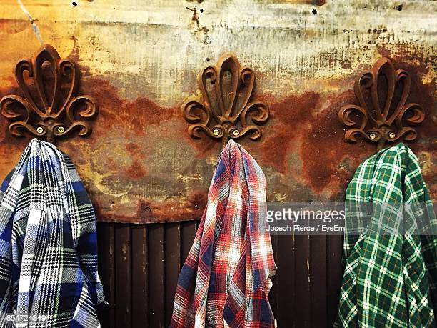 plaid shirts hanging from hooks mounted on rusty wall - karohemd stock-fotos und bilder