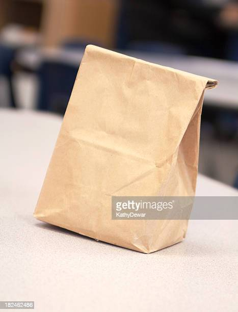 plain blank brown paper lunch bag on a table - sac stock pictures, royalty-free photos & images