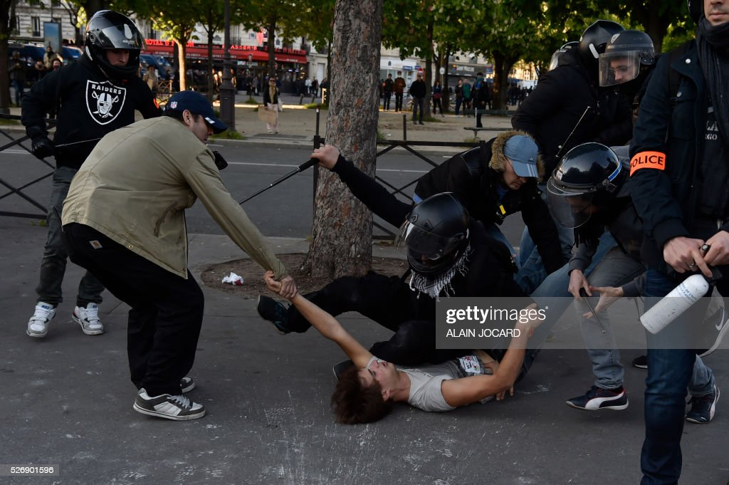 TOPSHOT - Plain cloth policemen arrest a man during clashes between anti-riot police and protesters during the traditional May Day demonstration in Paris on May 1, 2016. / AFP / ALAIN
