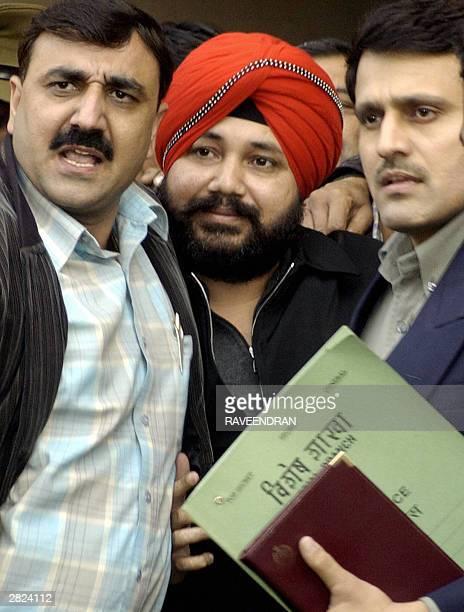 Plain clothed Indian police officers escort Indian singer Daler Mehandi as he arrives at Tis Hazari Court in New Delhi 20 December 2003 Police...