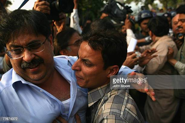 A plainclothed policeman detains a civil rights activist at an antigovernment protest on November 4 2007 in Islamabad Pakistan A small group of...