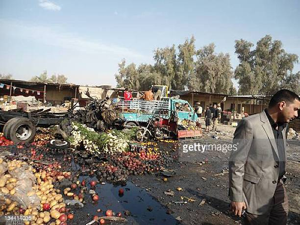 A plainclothes member of Iraqi security forces investigates the site of a car bomb explosion in a vegetable market in the central town of Khalis on...