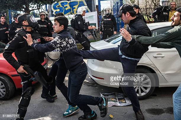 TOPSHOT A plainclothes police officer kicks a demonstrator as Turkish antiriot police officers disperse supporters in front of the headquarters of...