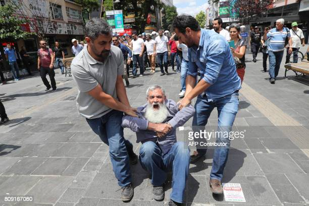 Plainclothes police officers detain a demonstrator during a protest against the detention of two hungerstriking teachers in Ankara on July 5 2017 A...