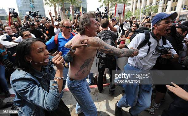 Plainclothes police remove a man with nazi skin tattoo's after he was beaten by an angry crowd of counterprotesters before the neonazi group The...