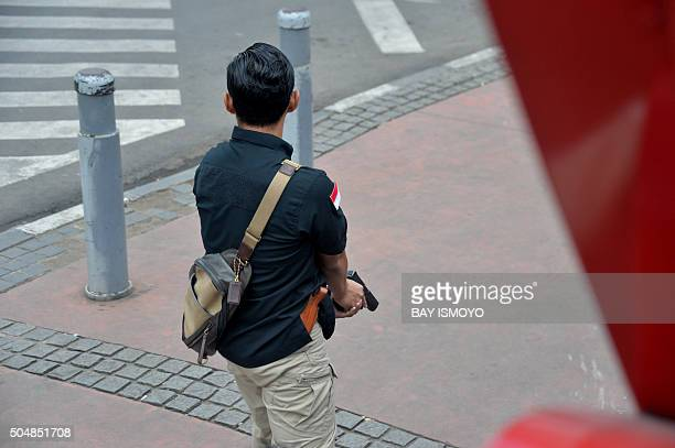 A plainclothes policeman prepares his handgun as authorities chase the suspects after a series of blasts hit the Indonesia capital Jakarta on January...