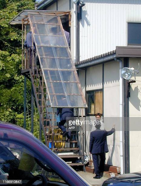 Plainclothes policemen enter an office related to alleged senior alQaeda French member Lionel Dumont in Niigata 250 kms north of Tokyo 26 May 2004...