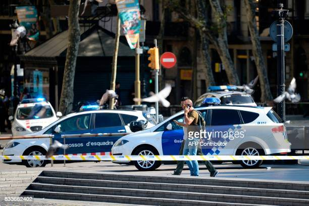 Plainclothes policemen phone as they walk past police cars in a cordoned off area after a van ploughed into the crowd injuring several persons on the...