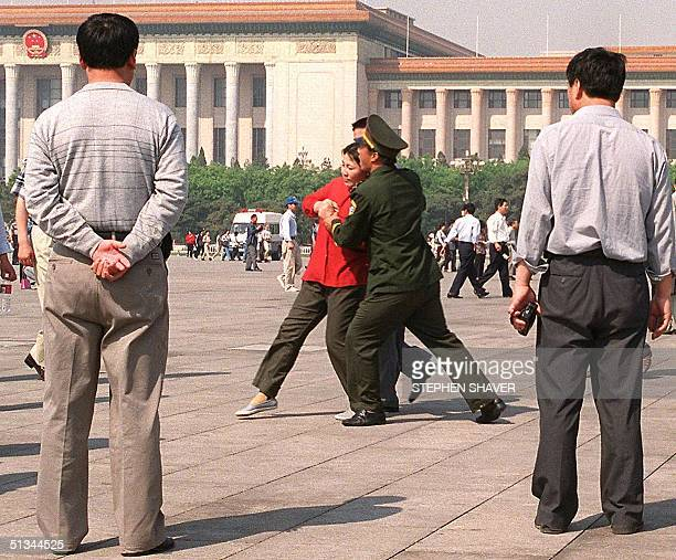 Plainclothes policemen watch as a female Falungong practioner resists arrest while being forced by police towards a police van 11 May 2000 in...