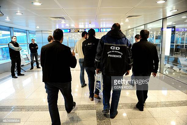 Plainclothes Turkish police officers detain passengers after a plane landed at the international airport in Istanbul on January 29 2015 The country...