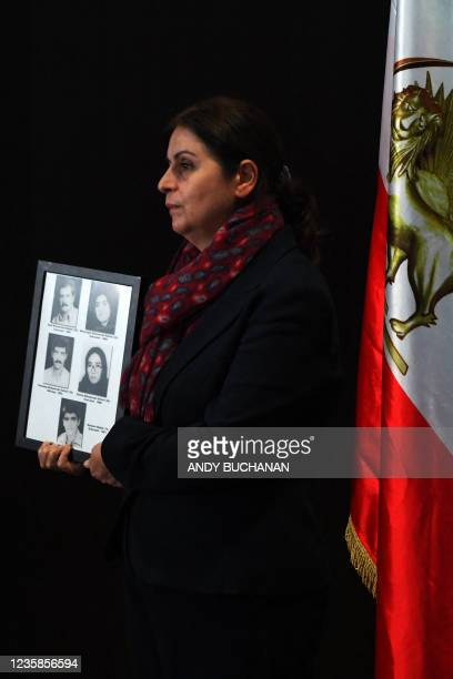 Plaintiff Farzaneh Majidi holds pictures of her executed family members as she attends a press conference organised by The UK Representative Office...