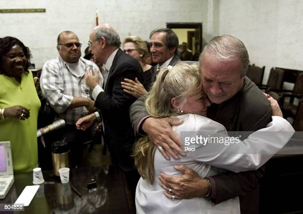 Plaintiff Ralph Della Vecchia right who's wife Angie died of cancer hugs Margaret Amodeo wife of plaintiff Frank Amodeo after the jury returned a...