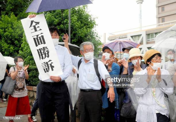 Plaintiff supporters celebrate after hearing the ruling by the Hiroshima District Court on July 29, 2020 in Hiroshima, Japan. A local court has...