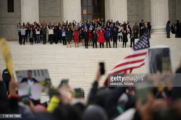plaintiffs come out of court as immigration rights activists take part in a rally in front of the US Supreme Court in Washington DC on November 12...