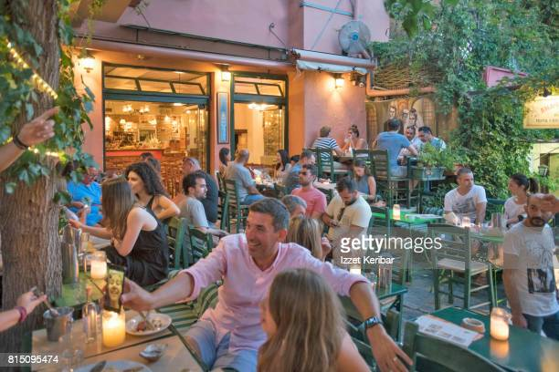 Plaka district  colorful people sitting at restaurants and stairs , Athens Greece