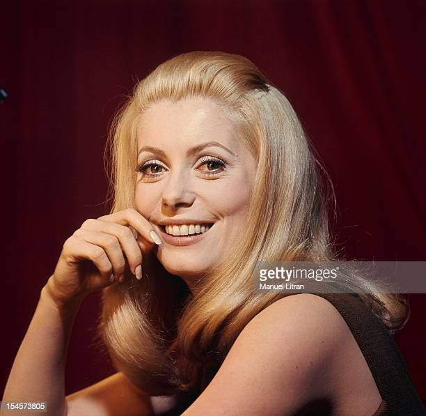 Plan smiling face of Catherine Deneuve in brown sleeveless dress one hand on the cheek during a break in the filming of 'Beautiful Day' by Luis Bunuel