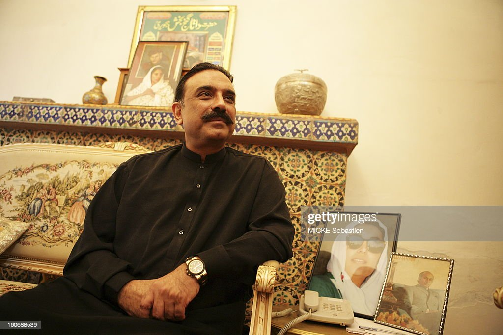 Plan three quarters Asif Ali Zardari smiling sitting in a lounge of the PPP (Pakistan People's Party) in Larkana, a framed portrait of his wife Benazir Bhutto has raised its ratings.