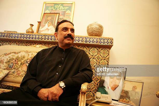 Plan three quarters Asif Ali Zardari smiling sitting in a lounge of the PPP in Larkana, a framed portrait of his wife Benazir Bhutto has raised its...