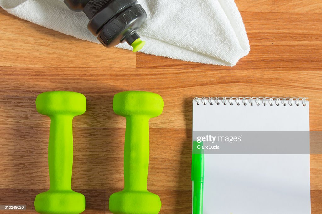 Plan workouts with dumbbells, towel, Water Bottle, Notepad on wooden : Stock Photo