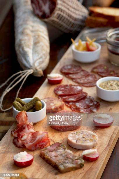 planchette de charcuterie; wild boar salami, pates and terrines; pickles - charcuterie board stock pictures, royalty-free photos & images