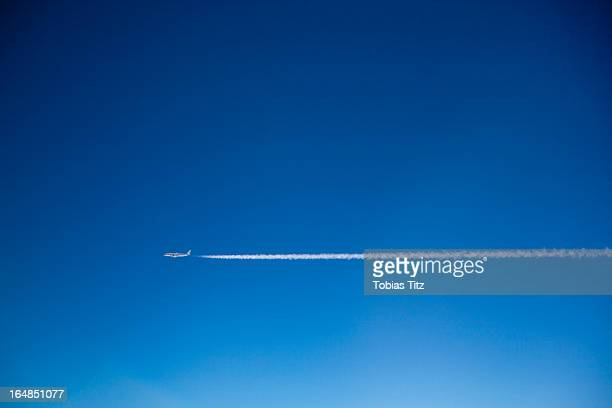 a plane and vapor trails in the sky - airplane sky stock pictures, royalty-free photos & images