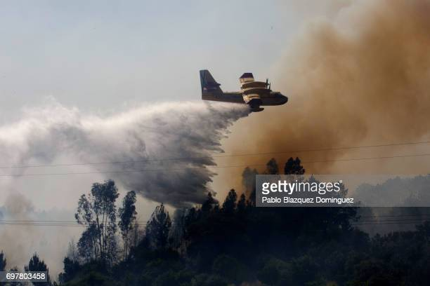 A plane battles a fire from the air after a wildfire took dozens of lives on June 19 2017 near Pedrogao Grande in Leiria district Portugal On...