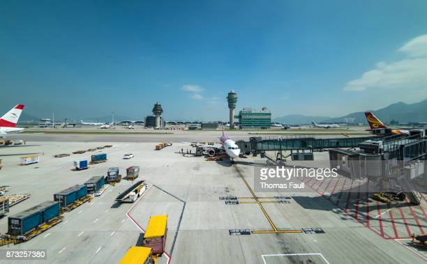 Plane being boarded at Hong Kong airport with the air traffic control tower