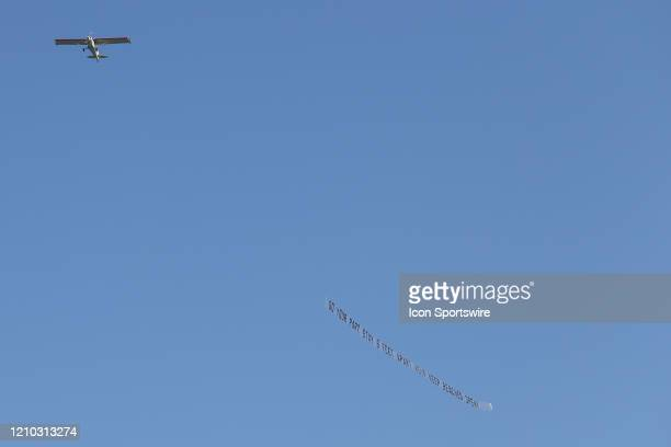 A plane carries a banner reading DO YOUR PART STAY 6 FEET APART HELP KEEP BEACHES OPEN over crowded the beaches in its first open hour on April 17...