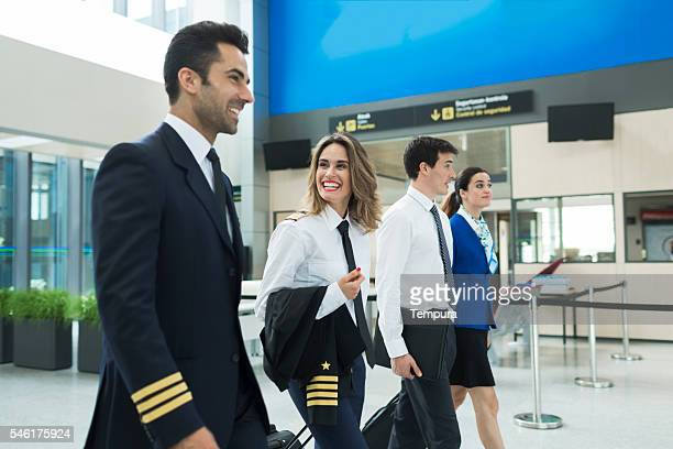 plane crew walking in airport terminal near airline office. - piloting stock pictures, royalty-free photos & images