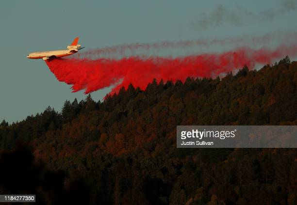 A plane drops fire retardant ahead of the Kincade Fire on October 29 2019 in Healdsburg California Fueled by high winds the Kincade Fire has burned...