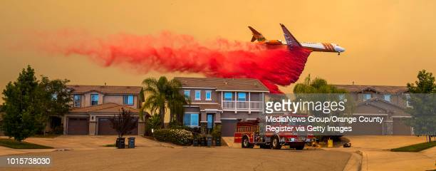 A plane drops fire retardant behind homes along Willow Ridge Court in Lake Elsinore as the Holy fire burned near homes on Wednesday afternoon August...