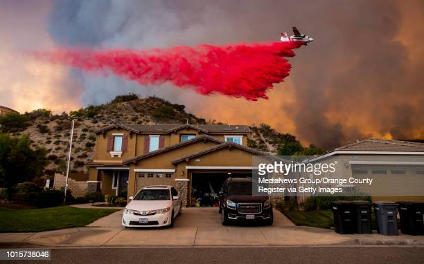A plane drops fire retardant in the Cleveland National Forest behind homes along Crystal Ridge Court in Lake Elsinore as the Holy fire burned near...