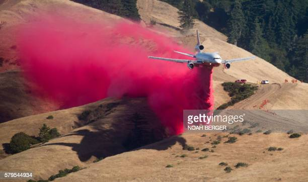 TOPSHOT A plane drops fire retardant while battling the Soberane Fire in Carmel Highlands California on July 23 2016 The fire has scored more than...